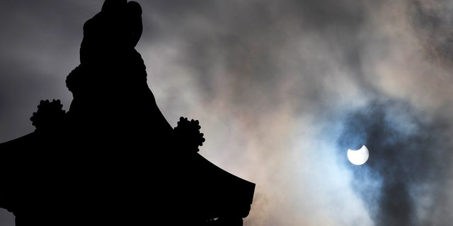 Nelson's Column in Trafalgar Square, London, is silhouetted by a partially eclipsed sun, Thursday June 10, 2021. (AP Photo/Frank Augstein)
