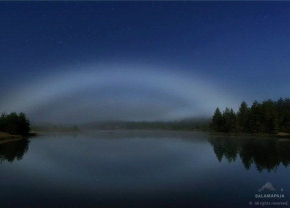 White arc in dark blue sky reflected in a lake bordered by evergreen trees.