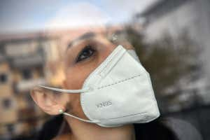 woman wearing face mask behind a window