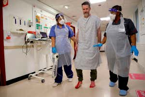 Two members of staff wearing perso<em></em>nal protective equipment at King's College Hospital in Lo<em></em>ndon assist a patient recovering from covid-19 with walking
