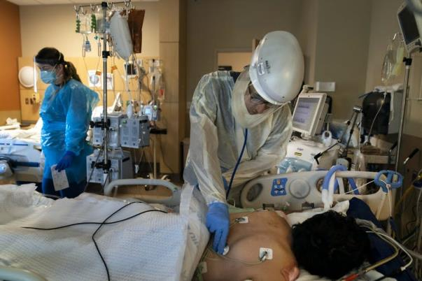 A medical worker in full protective equipment cares for a COVID-19 patient lying face down in a hospital bed.
